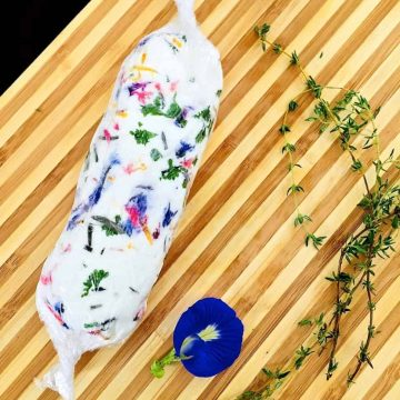 Party time deserves this Edible flower and herb butter. Here is it is rolled and wrapped like a sausage and kepto on a striped wooden board with a blue flower and some thyme sprigs alongside
