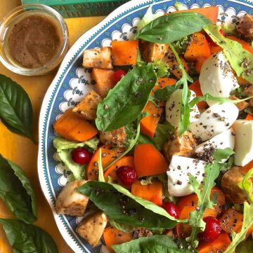 Autumn and Winter goodness of Persimmon and fresh mozzarella in a salad with mustard and balsamic vinegar and basil leaves on the side