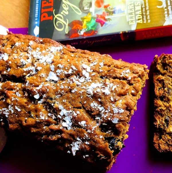 Easy Eggless Christmas Fruit Cake with no added sugar. Set on a purple sheet with a book on Pies on one side and a slice of the cake alongside