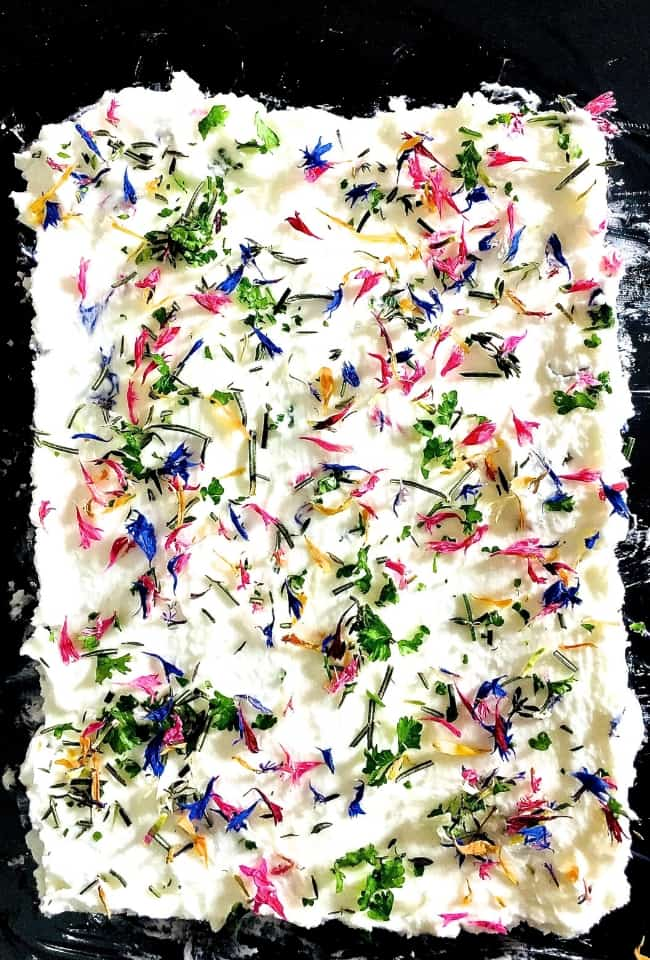 Party fare Edible Flower and Herb Butter with flowers and herbs strewn on butter for a spread or a dip