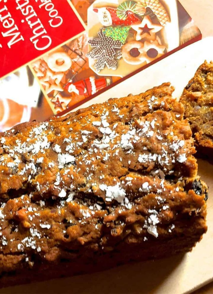 Brown coloured Eggless Christmas Cake with icing sugar strewn on top. A slice of cake lying on a wooden board, to the right and a red white and green book on Christmas cookies in the background