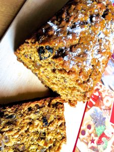 Christmas Fruit cake with no eggs and no added sugar, sliced and on a wooden board with a book of Christmas recipes alongside