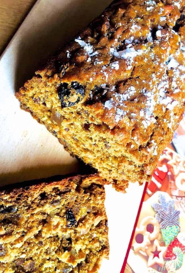 An eggless Christmas Fruit cake sliced and ready for serving. Studded with fruits that have been soaked before baking