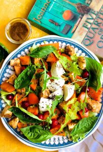 Orange green and white persimmon, mozzarella and basil make up this persimmon mozzarella salad shown on a blue edged plated with a green and orange book on one side and a bowl of mustard balsamic dressing on the other
