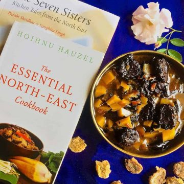 A brass bowl with aloo badi, a Manipuri dish of potatoes and little sundried nuggets of black gram lentil paste, on a purple background and book on the North East Indian cuisine alongside