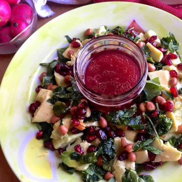 Avocado Fenugreek Leaves Salad with Peanuts, feta and pomegranate arranged on a green plate with pink dressing in the centre and reddish pink radishes in a bowl