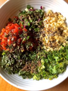 A bowl with portions of bulgar, tomato, parsley, romaine lettuce seasoned with pepper and salt, ready to be mixed into Tabbouleh