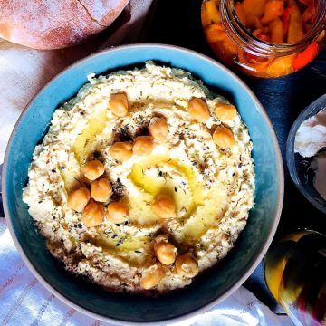 A large shallow blue bowl of creamy yellow hummus with olive oil and chickpeas for garnish, with a plate of pita bread, a jar of roasted red peppers, bowl of goats cheese and jar of olives surrounding