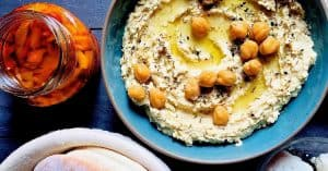 A wide blue bowl of a pale creamy yellow hummus, with chickpeas and olive oil for garnish and with a plate of pita bread and a jar of roasted red peppers alongside
