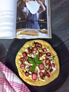 A book with a recipe and image of pizza being made, along with strawberry goat cheese pizza baked and shown with red striped napking
