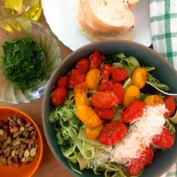A bluish green bowl with fettuccine pasta covered with pesto, topped with a sauce of red and yellow cherry tomatoes and parmesan