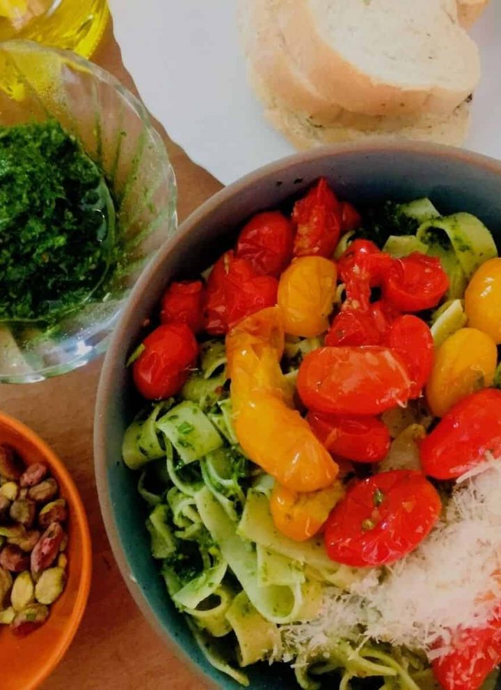 Arugula Pesto Pasta in Cherry Tomato Sauce:A bluish green bowl with fettuccine pasta covered with pesto, topped with a sauce of red and yellow cherry tomatoes and parmesan