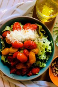 A large blue bowl heaped with arugula pesto pasta, topped with a sauce of red and yellow cherry tomatoes and grated parmesan. Olive oil, pesto and pistachios arranged on one side