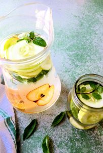 A tall glass jug of water with round slices of cucumber some lemon and sprigs of mint and a smaller jar with cucumber and mint