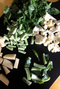 Ingredients for making the Bai or veg stew spread on a black wooden chopping board- cauliflower stalks, florets, leaves, potato and beans