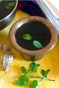 A brass tumbler (traditional cup) with dark jaggery water or panakam, with 2 fresh green tulsi leaves floating. A piece of dry ginger and some more tulsi leaves, the edge of a black bowl and some white fabric are seen around the tumbler