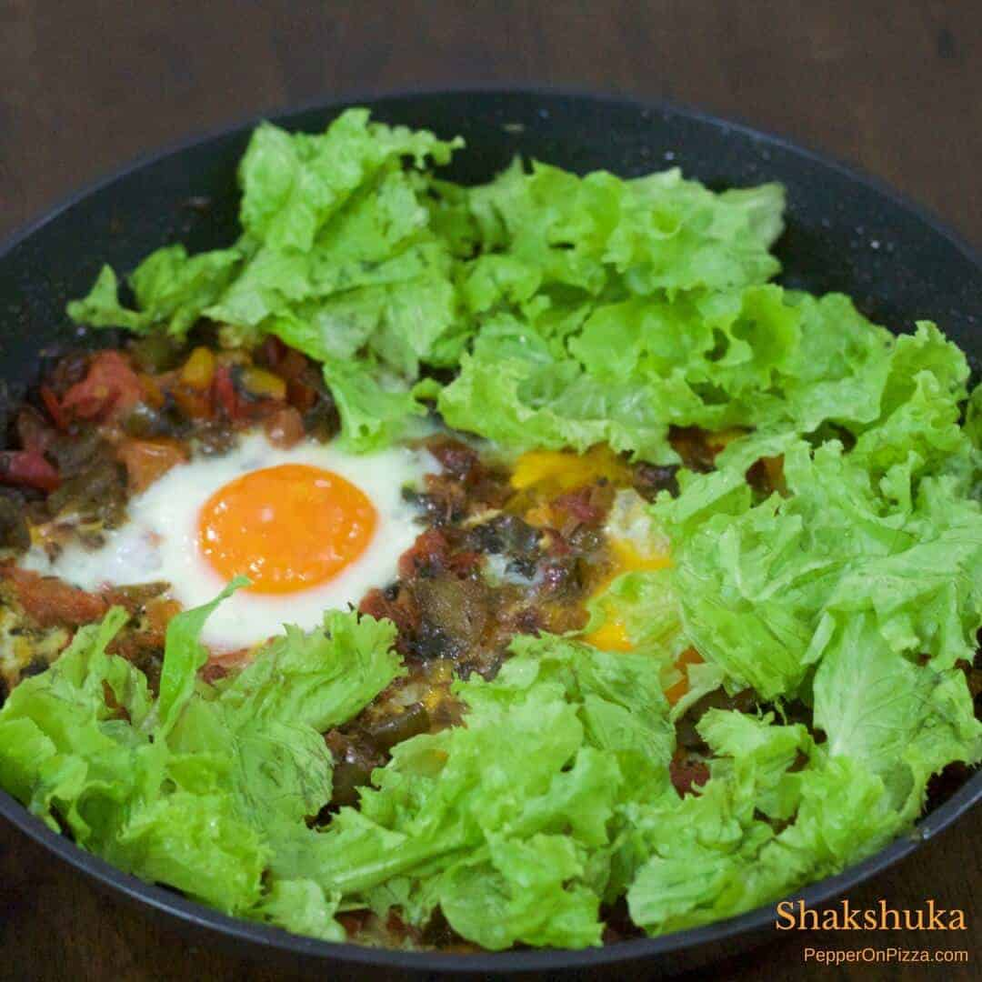 A pan with classic Shakshuka of eggs poached in sauteed tomatoes and red peppers, with a layer of green lettuce arranged along the sides of the pan. Gluten free, easy, delcious