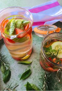 Two glass jars with slices of pink strawberries and with a round slice of cucumber floating on top of one jar. Basil leaves in one and rosemary and mint in the other