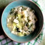 A green bowl with white slices of cooked colocasia, green bits of cabbage and mustard greens in a cloudy liquid. A green and white stirped napkin below and the whloe on a green background