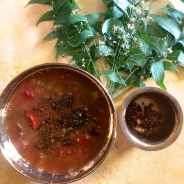 Brass bowl with reddish brown liquid rasam with tomatoes and fried neem flowers seen on the surface. Fresh neem leaves in the background and a brass cup on the side with fried neem flowers. All on a yellow background