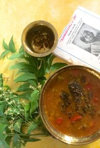 A brass bowl with brownish fluid Rasam, tempering of mustard, Fried neem flowers and cooked red tomato seen on top of the rasam. A bunch of fresh green neem leaves and flowers to the left and a brass bowl of fried neem flowers above along with a traditiona cookbook on Tamil Cuisine top right, all on a yellow background