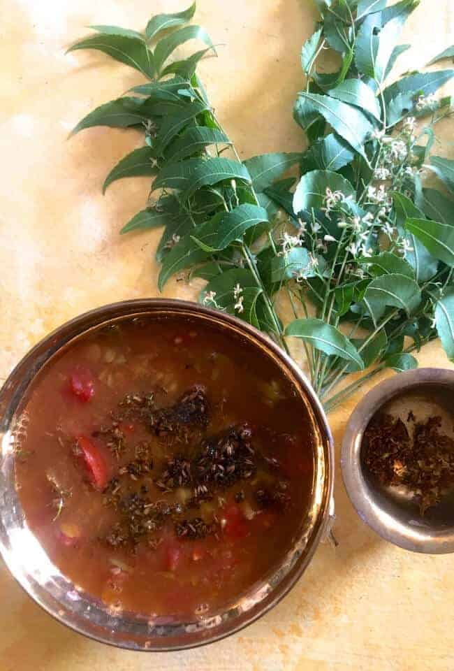 A bunch of fresh green neem leaves and flowers on a pale yellow background, with a braww bowl of brown coloured rasam, a fluid spicy tamarind dish. Red tomato slices, tempering of mustard seeds and neem flowers in ghee, seen on top of the rasam. A small brass bowl of fried neem flowerst o the right