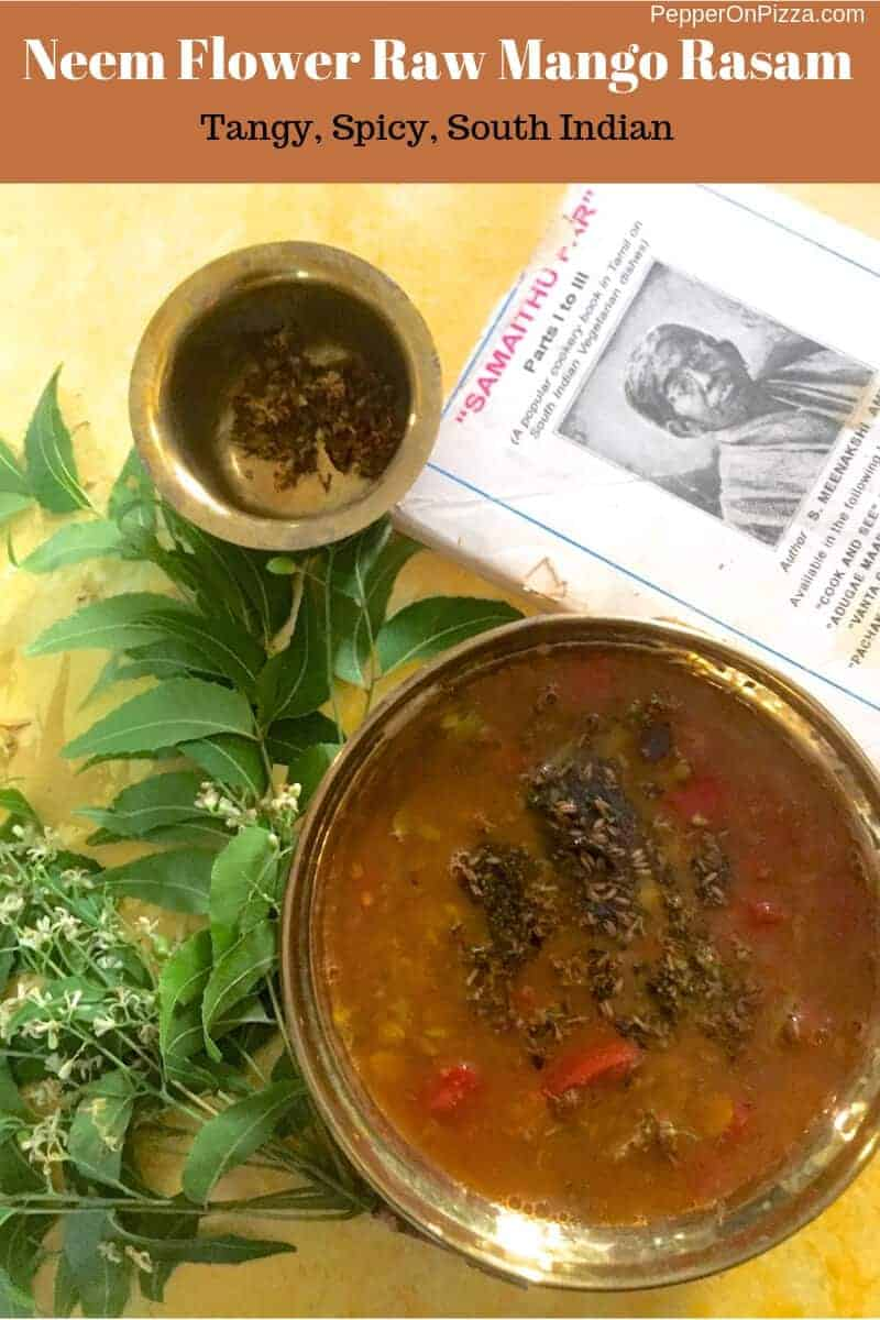 A brass bowl with brownish liquid neem flower raw mango rasam, tempered with neem flowers fried in ghee, mustard, cumin seeds, curry leaves and red pieces of tomato visible on top. A traditional tamil cookery book with a white cover to the left with a black and white image of the author. A little brass bowl with fried neem flowers on the left with a bunch of neem (margosa) leaves and flowers