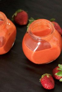 Two little jars of orangey pink strawberry poppyseed dressing, with strawberries strewn around them, all on a black background