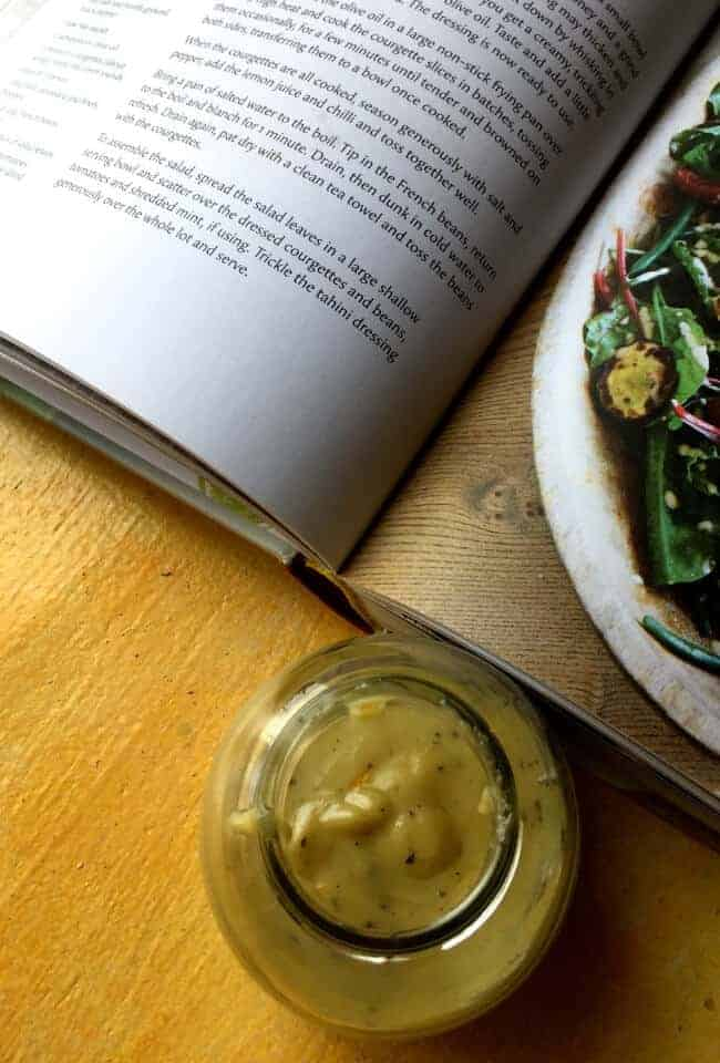 A small jar of creamy yellow salad dressing of tahini and citrus juices.A large cook book open beside, with part of a recipe for the salad dressing, and a part of a green salad on the facing page