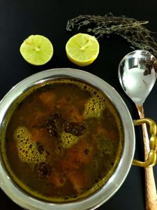 A bowl of dark fluid lemon thyme rasam with tomato, thyme leaves and mustard tempering seen on the surface. Two lemon halves above along with twigs of fresh thyme. A brass spoon to the right