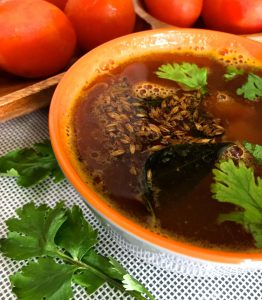 Brown fluid Tomato rasam in a grey bowl edged with orange, green fresh coriander leaves and a tempering of mustard and cumin seeds on the surface. A tray with red tomatoes top left and a few coriander leaves scattered bottom left, all on a white netted surface