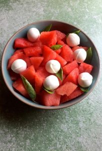Bright red watermelon cubes and white spheres of mini bocconcini cheese in a blue green bowl edged with brown, on a green background. This Watermelon Bocconcini salad is gluten free and garnished with arugula leaves and basil
