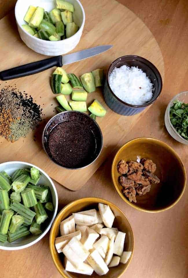 Ingredients for making the Traditional Besar or Besara - indigenous vegetables - slices of raw banana, parwal/potola or pointed gourd, drumstick, the traditional Odisha spice mix panch phutana, mustard seeds soaked for making mustard paste, moringa leaves, coconut and urad dal badi each in small cups, a knife for slicing veggies, resting on a cutting board