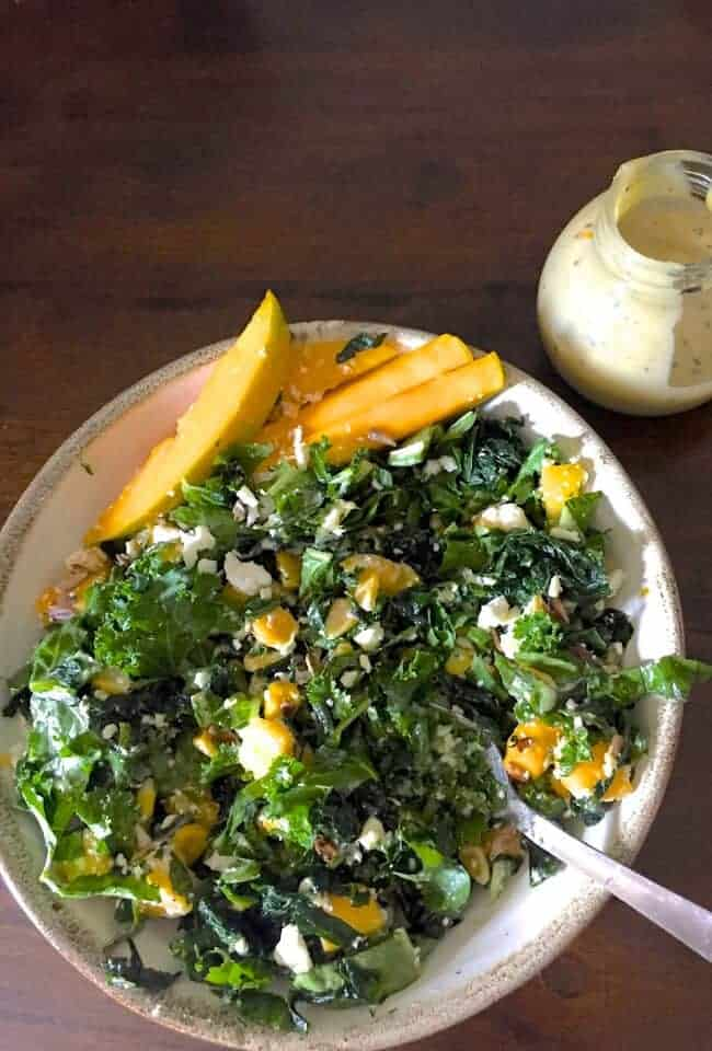 Massaged and marinated Kale mango salad with slices and cubes of ripe yellow mango and green kale, salad greens, yellow corn and white feta cheese. A small glass jar with cream coloured tahini dressing to the top right. All on a brown background