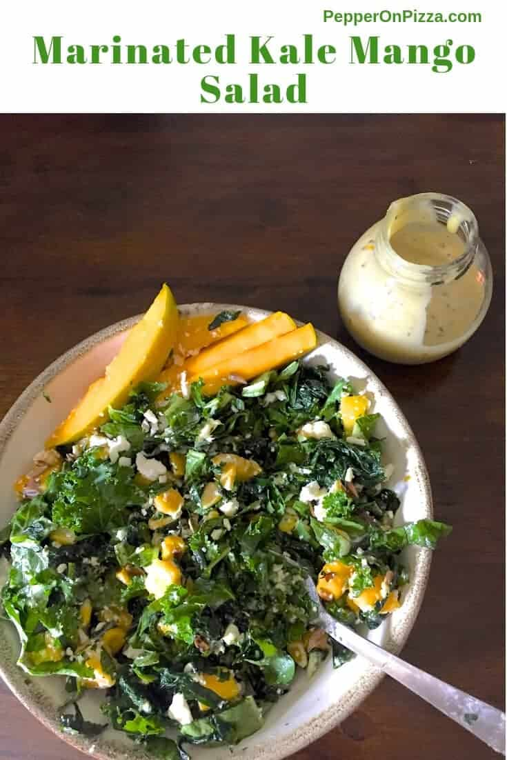 Marinated Kale Mango Salad served on a white plate with slices of yellow ripe mango heaped to the left of the plate. Cubes of mango seen among the green kale and salad greens on the plate. A small jar of creamy tahini citrus dressing on the top right, all on a dark brown background
