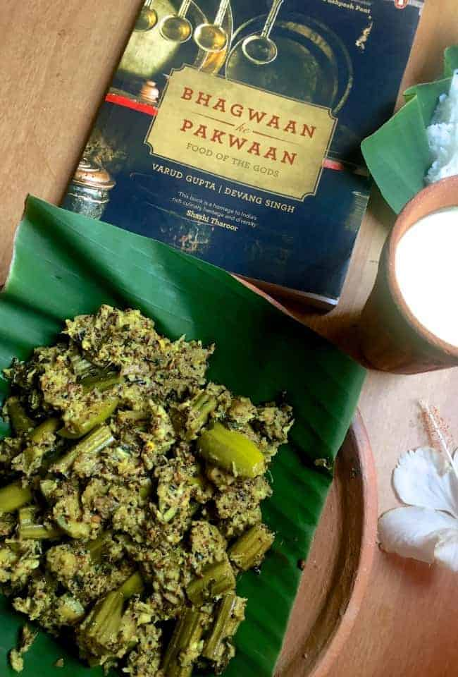 A black coverd book with red letters on a yellow background, 'Bhagwaan ke Pakwaan' and in the foreground a Besara vegetable curry on a green banana leaf on a clay plate, a white hibiscuis flower, cooked rice on another banana leaf and clay glass with yellow mango lassi