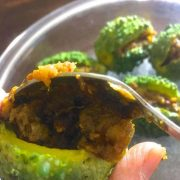 A baby bitter gourd/ karela held by the fingers while a stainless steel spoon of stuffing is being filled in. Other stuffed baby karela in the background