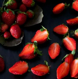 Ovehead shot of bright red strawberry halves and a large grey green leaf with whole strawberries, set against a black cutting board