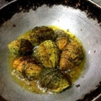 Process shot: A batch of small bitter gourd/ karela being shallow fried in mustard oil, in a cast iron frying pan
