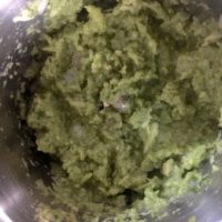Process shot: Raw mango, onion and other ingredients being ground in a food processor into a green paste