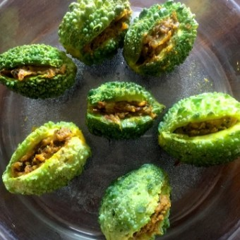 Process shot: Small bitter gourds stuffed with mustard coloured raw mango and onion filling, ready to be cooked