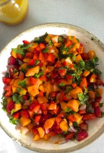 A white bowl seen from overhead, with bright coloured slices of orange yellow mango, red strawberry and flecks of green basil and coriander leaves