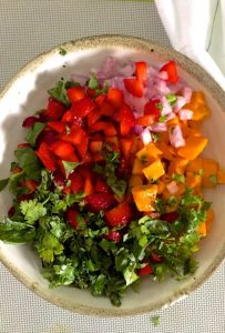 Sliced ingredients for the salsa, before being tossed together - orangey yellow mango, red strawberries, green basila and cilantro and pink onion