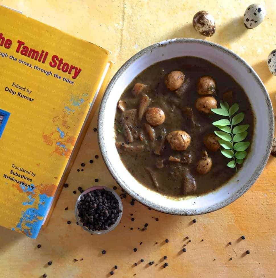 Kaada Muttai Milagu Kuzhambu: A white bowl with quail eggs in a pepper tamarind gravy. A yellow covered book with the name 'The Tamil Story' in Red, on the left and a bowl of pepper and scattered peppercorns in the foreground. A few speckled quail eggs in the background