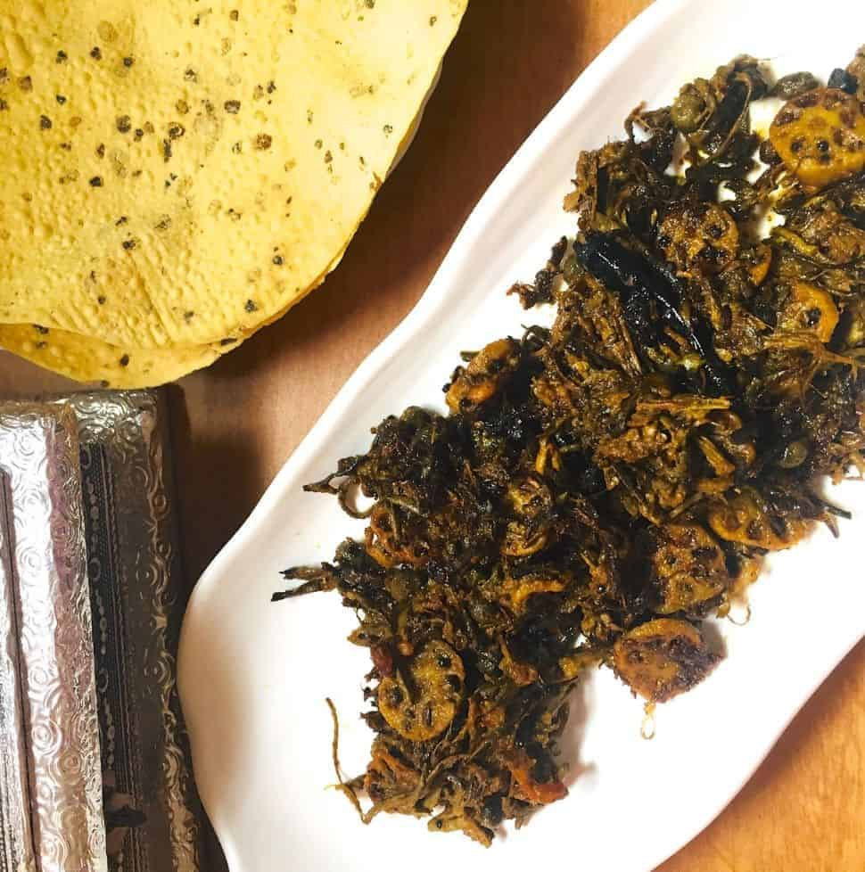 A plate of brown fried dry vegetables, Ker Sangri (berries and beans) and lotus stem slices on a long white plate with scalloped edges. A silver edged box and roasted pappad in the background