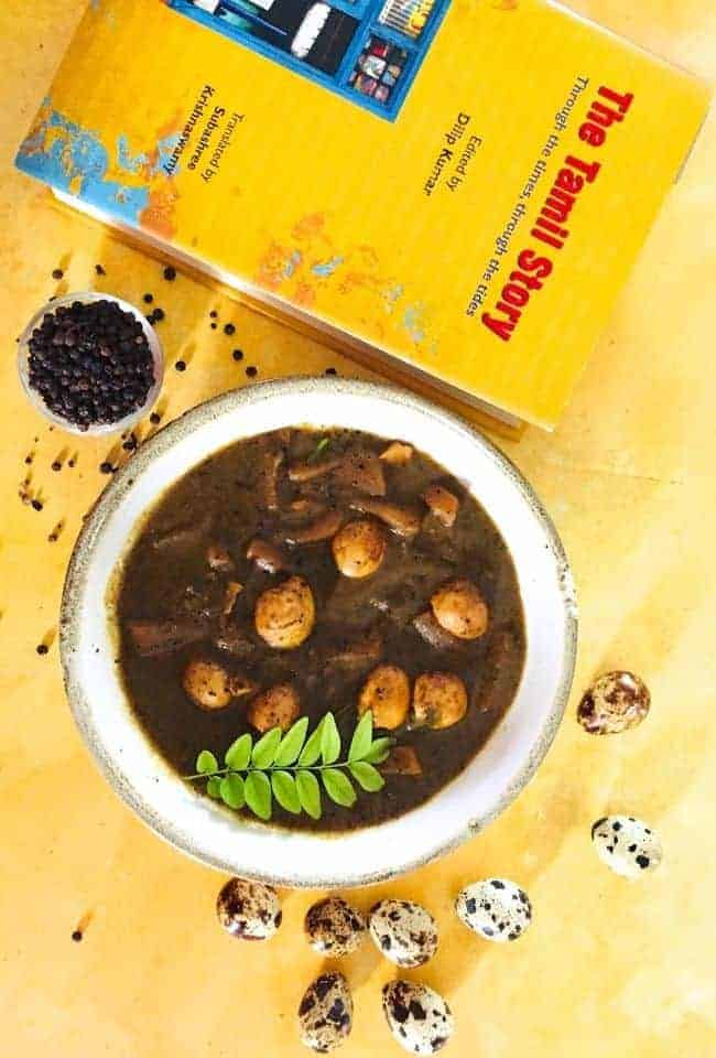 A bowl of dark brown coloured pepper gravy with quail eggs and potatoes and a sprig of curry leaves on top.All on a yellow background with a yellow coloured book called The Tamil Story (in red letters) in the background. A pot of black peppercorns and scatter pepper are behind the bowl. Some quail eggs are in the foreground