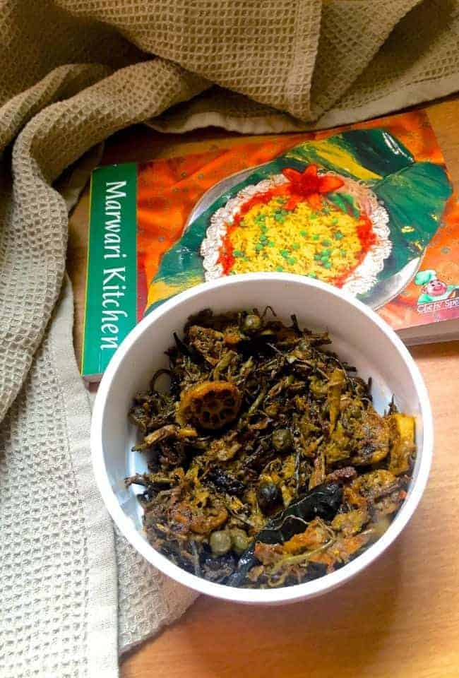 Rajasthani Ker Sangri, a brown coloured curry of dried berries and bean pods, in a white bowl. A book, Marawari Kitchen in the background and a dull grey napkin on the side