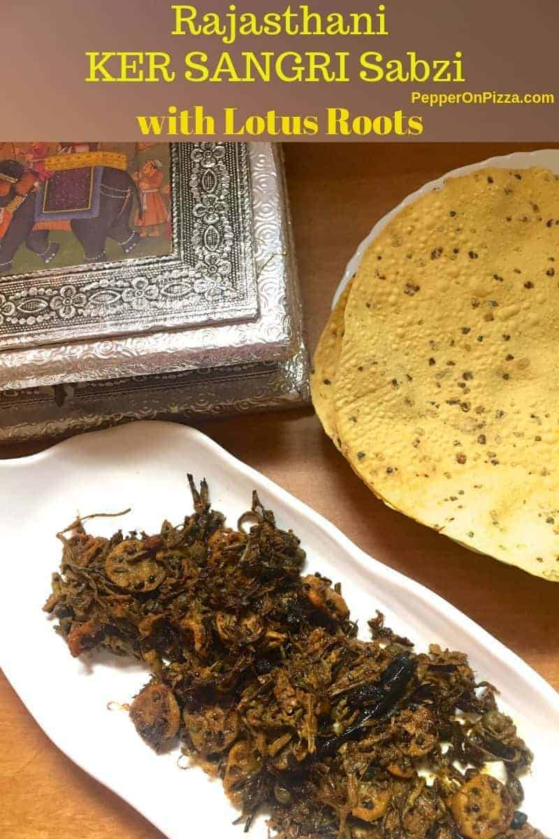 A white plate with scalloped edges with brown coloured dry vegetable curry , Ker Sangri, of berries and beans with lotus stem. A box showing a lid with a painted elephant on an orange background and silver coloured work all around and a plate of roasted pappad, in the background.https://www.PepperOnPizza.com