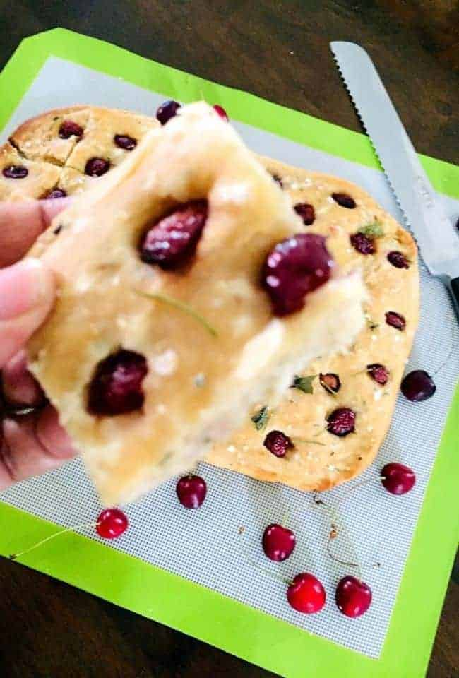 A slice of creamy yellow Focaccia bread studded with cherry halves, and a freshly baked focaccia seen below on green edged mat, with cherries scattered on it