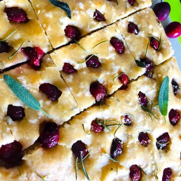 Sliced Savoury Cherry Focccia garnished with sage leaves.